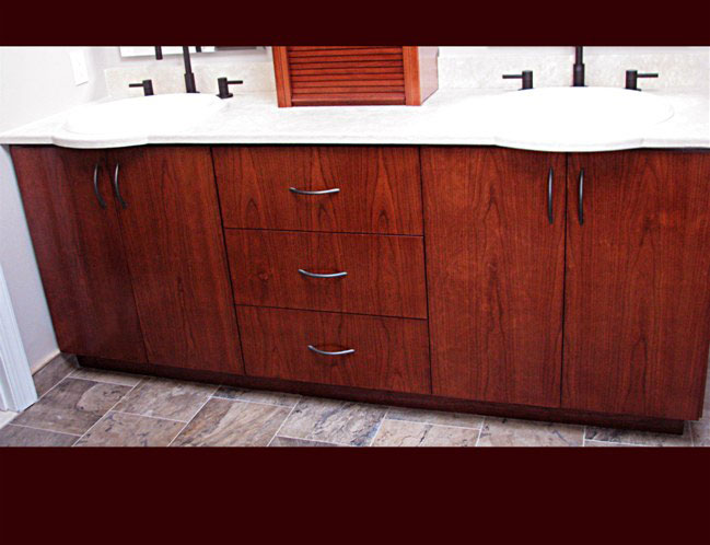 Stained Cherry Bathroom Vanity. Double sink with center drawers. Above vanity upper cabinet.