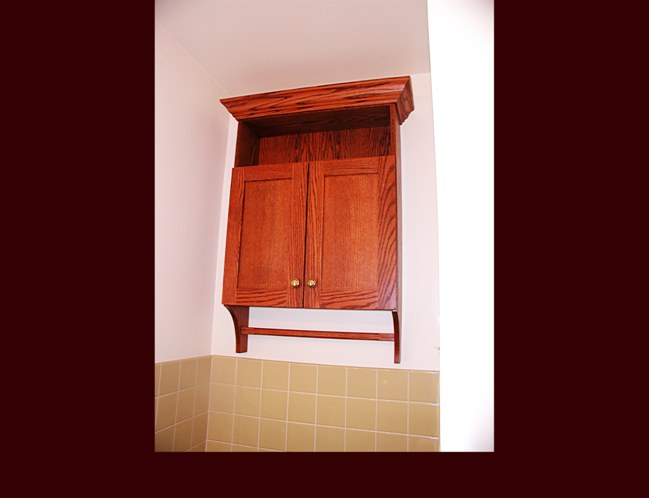 Oak Flat Panel Bath Cabinet with towel bar. Dyed finish. Crown Moulding. Over toilet storage.