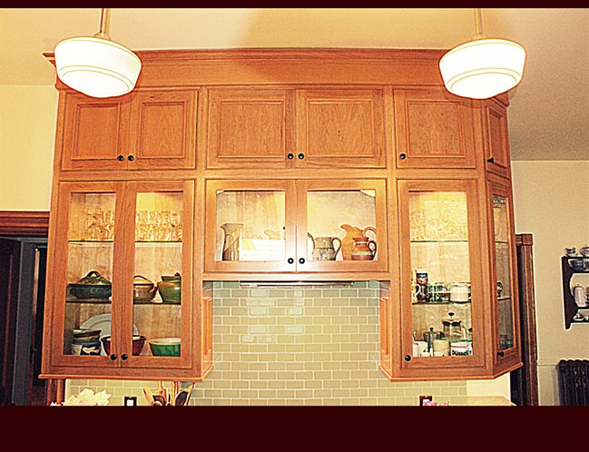 Custom Cherry Cabinets. Glass door cabinets with glass shelving and interior lighting. Light rail throughout.