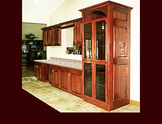 Custom Stained Mahogany Bar Cabinetry. Raised Panel door style. Full height media center with black glass. Decorative end panels. Crown Moulding.